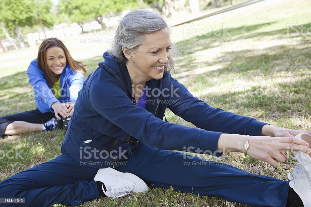 Women Stretching Legs While Exercising at a Park royalty-free stock photo