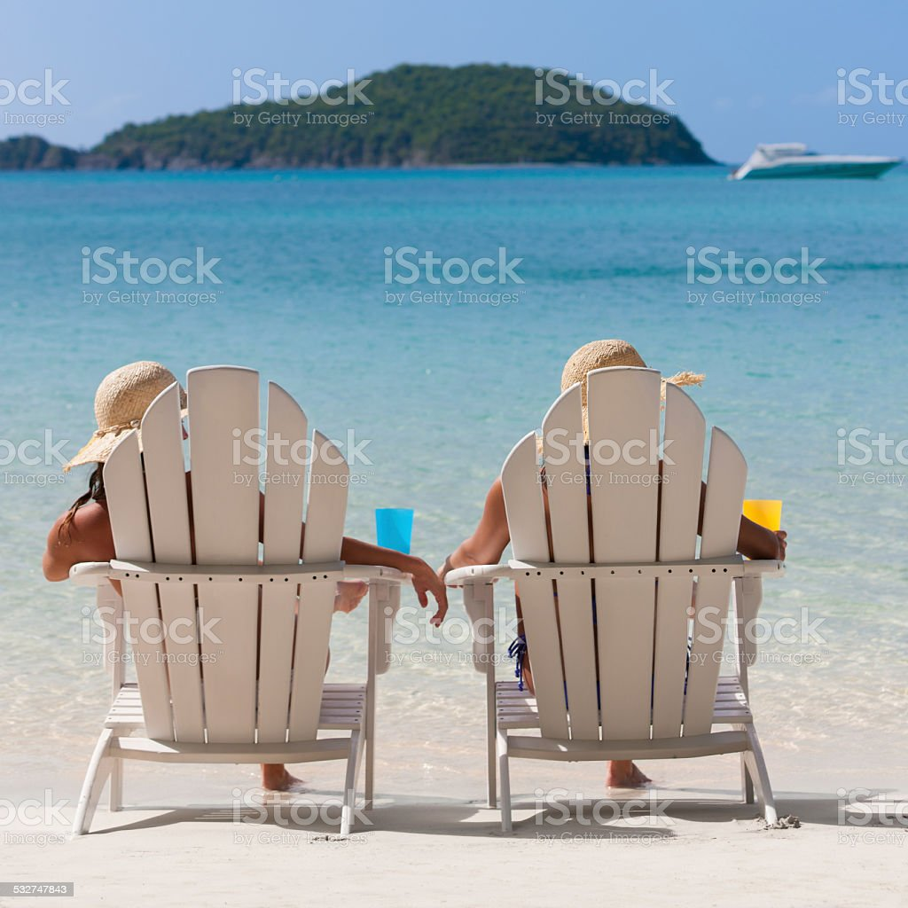 Women Sunbathing In Adirondack Chairs At A Caribbean Beach Royalty Free  Stock Photo