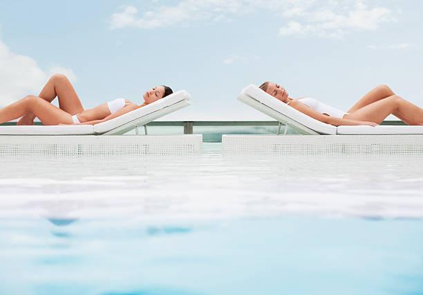 frau sonnenbaden in liegestühlen am pool - traum pools stock-fotos und bilder