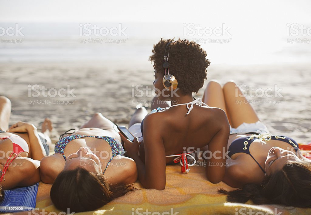 Women sunbathing together on beach stock photo