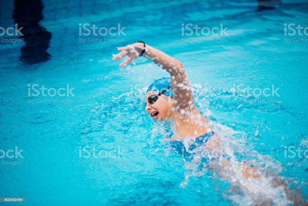 Female swimmer on evening training on swimming pool, warming up,...