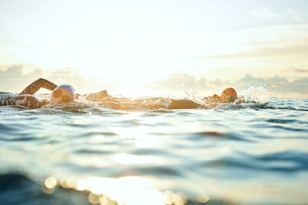women swimming in sea against sky during sunset - nuoto mare foto e immagini stock