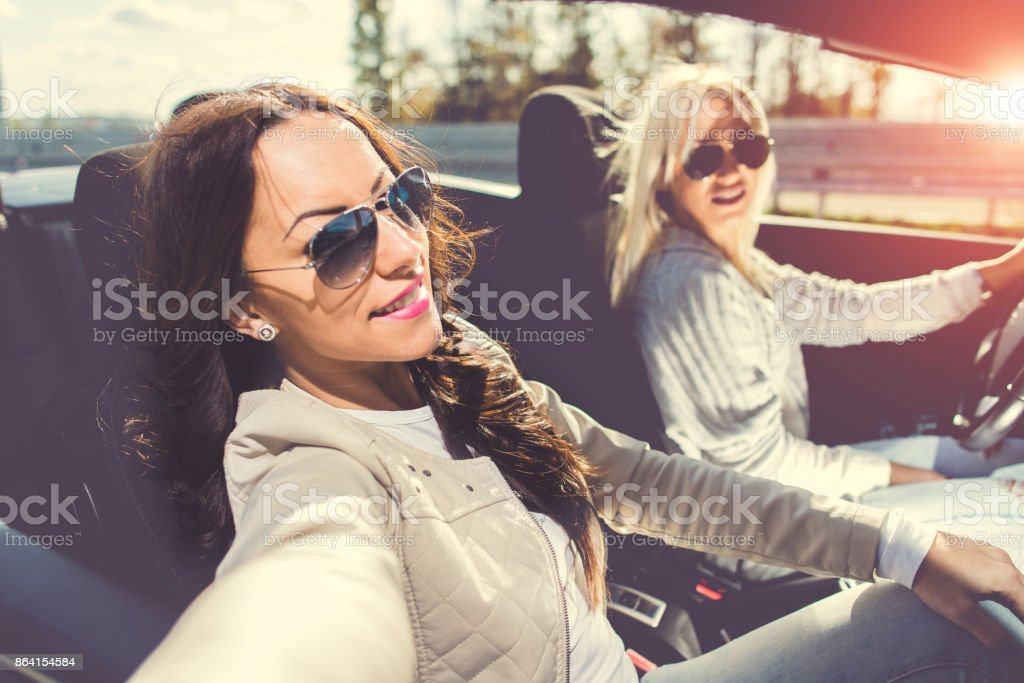 Women taking a selfie in a convertible car royalty-free stock photo
