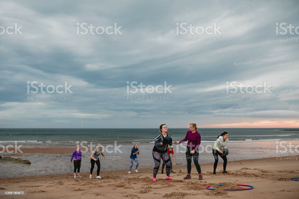 Women from a sports boot camp all taking part in a mini sports...