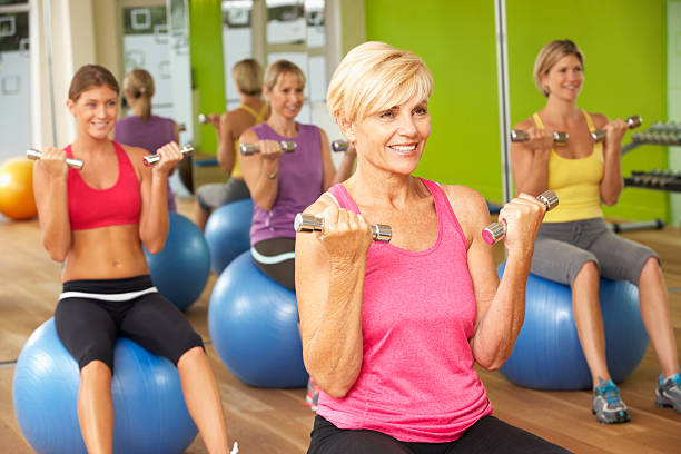 Women Taking Part In Gym Fitness Class Women Taking Part In Gym Fitness Class Looking Ahead exercise class stock pictures, royalty-free photos & images