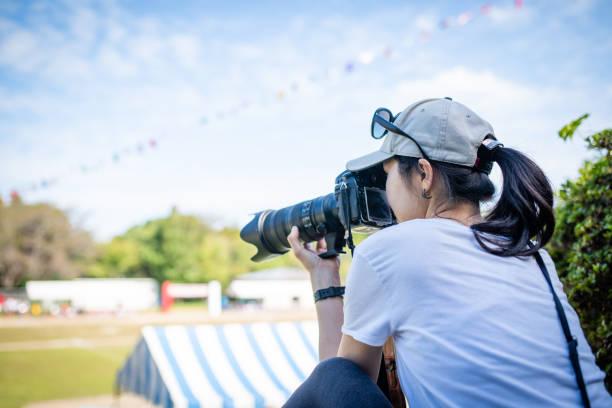 vrouwen nemen foto's bij athletic meet - telelens stockfoto's en -beelden