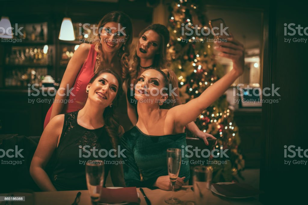 Women taking selfie at dinner party stock photo