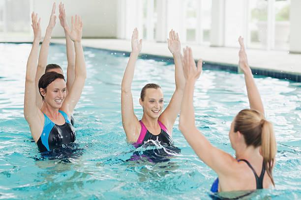 Donne prendendo la classe di aerobica in acqua in piscina - foto stock