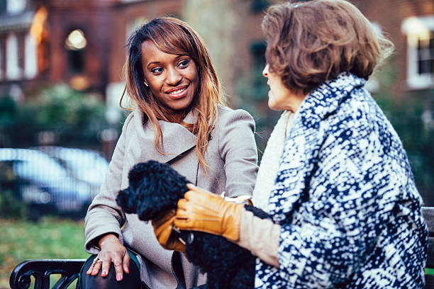 Women Talk Young woman and senior woman with a dog on bench in a park. They are talking and having fun. age contrast stock pictures, royalty-free photos & images