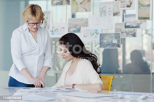 istock Women talking at table in design office 1148559068