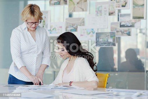 519523970istockphoto Women talking at table in design office 1148559068