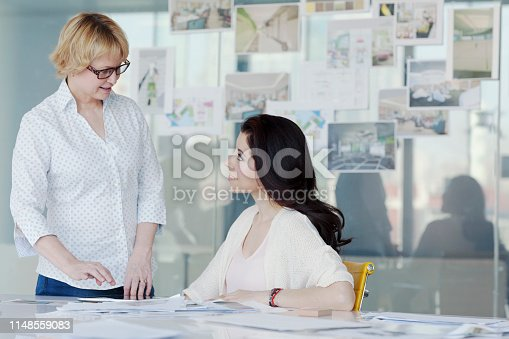 istock Women talking at table in design office 1148559083