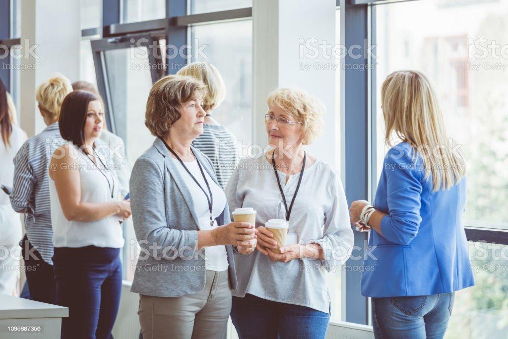 Women talking during a break in seminar Group of women talking during a break in seminar. Business women chatting in office lobby during break. Adult Stock Photo