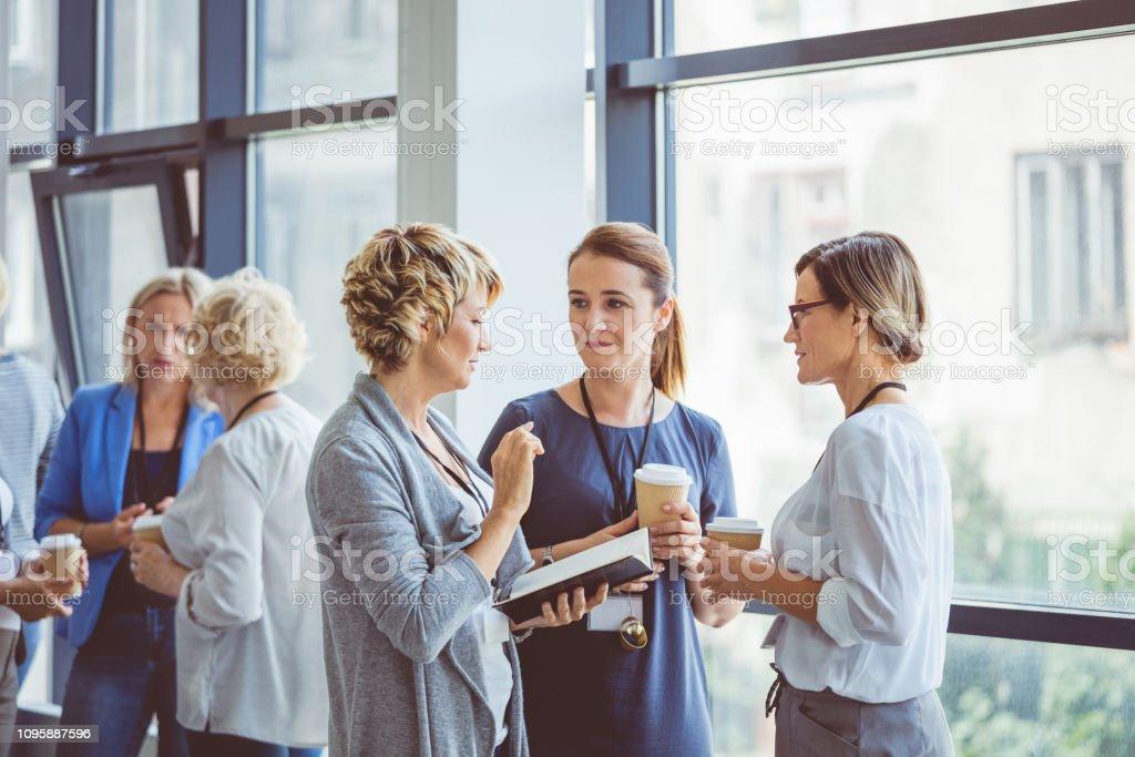 Women talking during coffee break at convention center Group of women talking during coffee break at convention center. Break during a women seminar. Adult Stock Photo