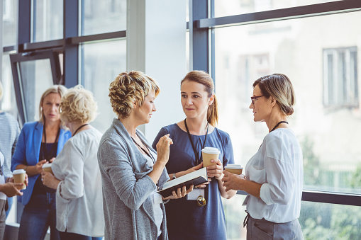 Women Talking During Coffee Break At Convention Center Stock Photo - Download Image Now