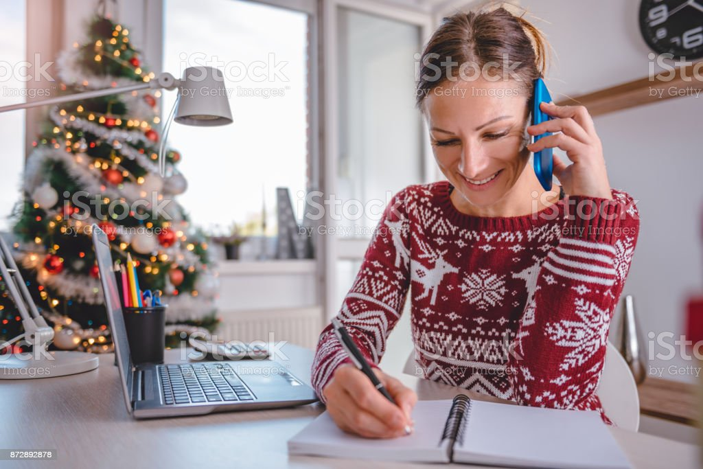 Women talking on smart phone and writing notes stock photo