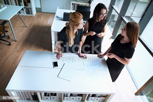 istock Women talking together in design planning office 637869830