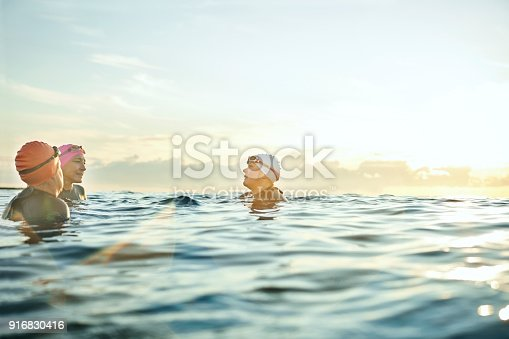 Female friends wearing swimming caps while talking in sea. Women are enjoying vacation during sunset. Swimmers are at beach against sky.