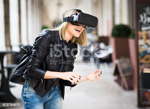 istock Women testing Virtual Reality simulator on the street 623784670