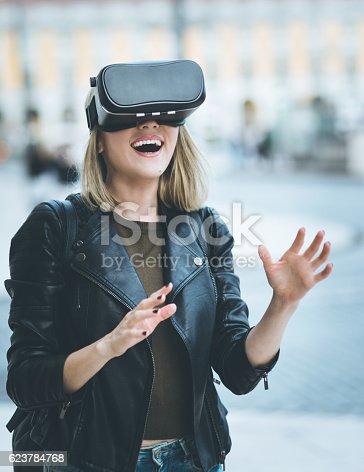 istock Women testing Virtual Reality simulator on the street 623784768