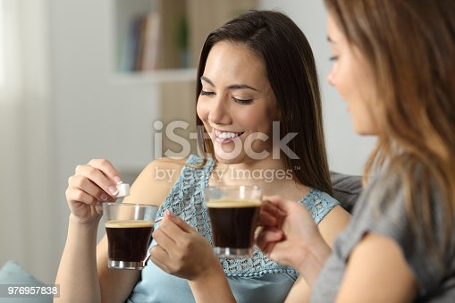 Women throwing sugar cube into coffee sitting on a couch in the living room at home