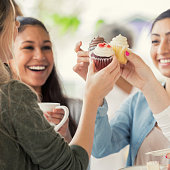 Young women 'toast' cupcakes while attending a bake sale benefitting cancer research and awareness.