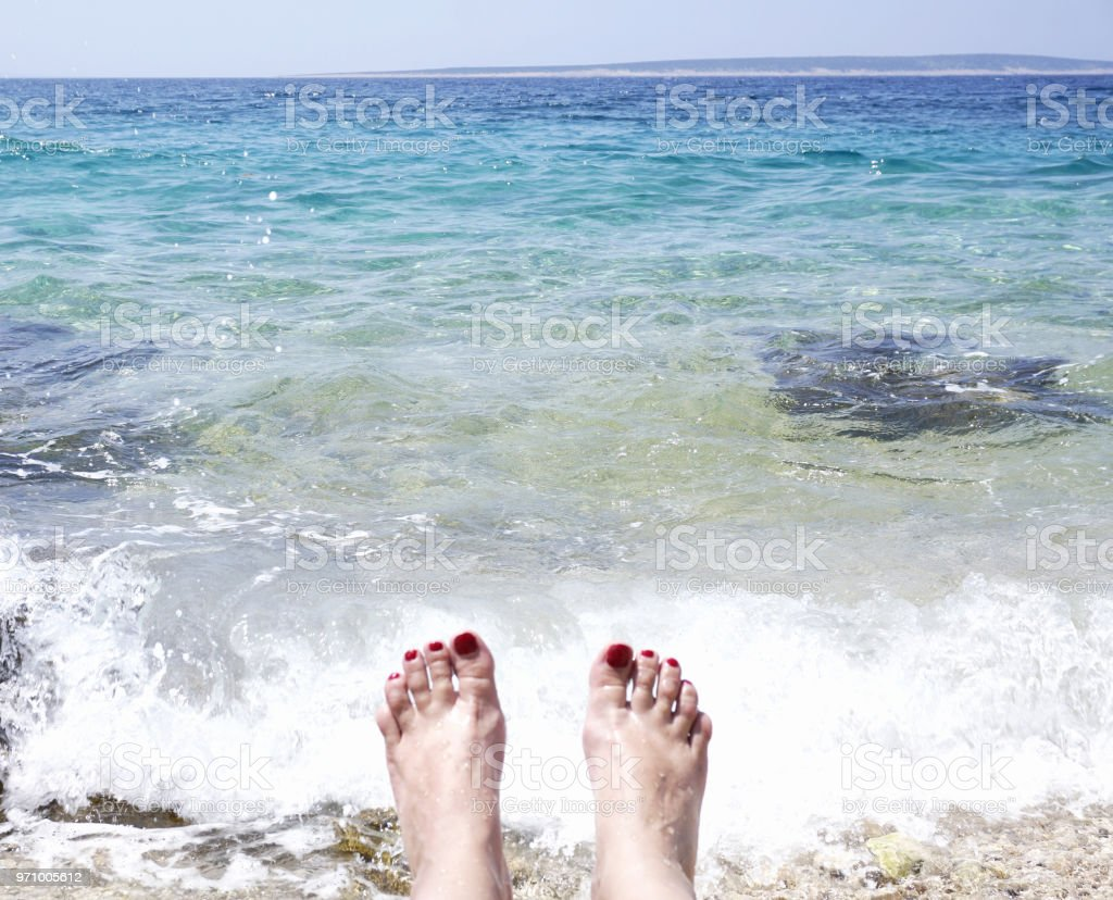 Women toes in the sea foam on the beach stock photo
