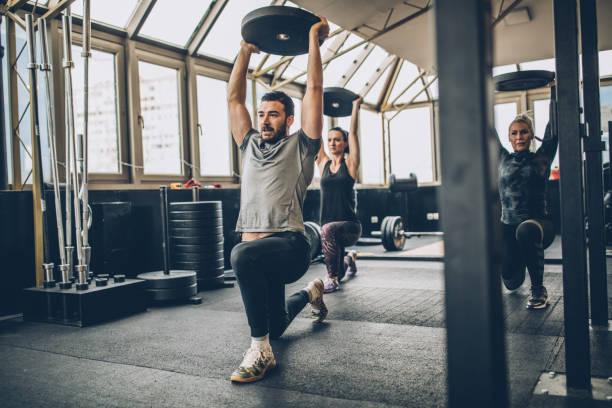 kvinnor tillsammans med fystränare i gymmet - tyngdlyftning bildbanksfoton och bilder