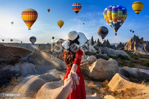Women tourists holding man's hand and leading him to hot air balloons in Cappadocia, Turkey.
