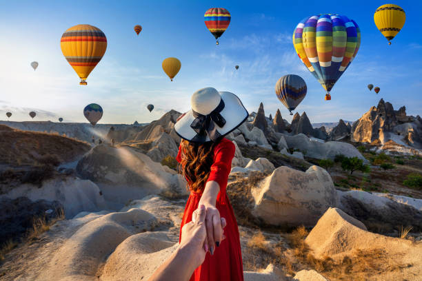Women tourists holding man's hand and leading him to hot air balloons in Cappadocia, Turkey. stock photo