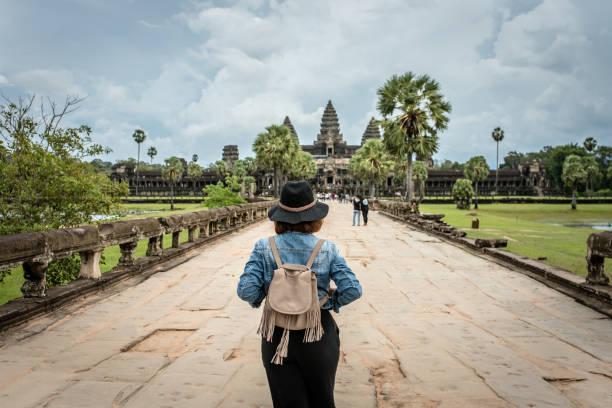 Women tourists wear jacket jeans walking into Angkor Wat landmark in Siem Reap, Cambodia. Angkor Wat inscribed on the UNESCO World Heritage List in 1992 – Foto