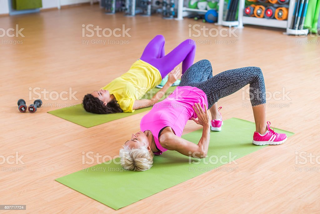 Women training their glutes by doing bridging exercise on mats stock photo