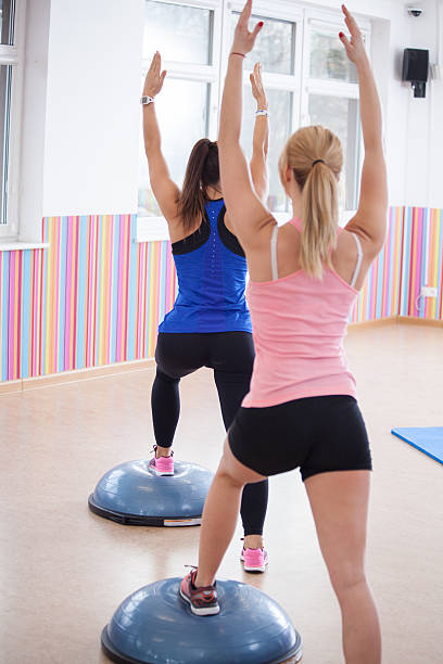 Women training with bosu ball stock photo
