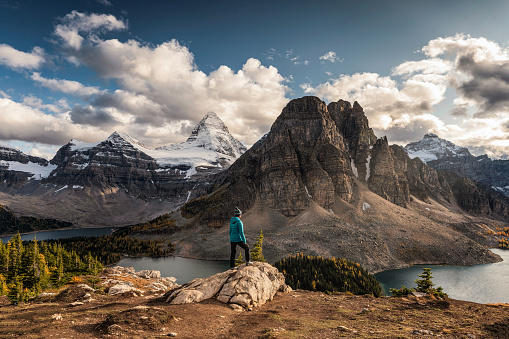 Women traveler standing on cliff with Mount Assiniboine on Niblet in provincial park at Alberta, Canada