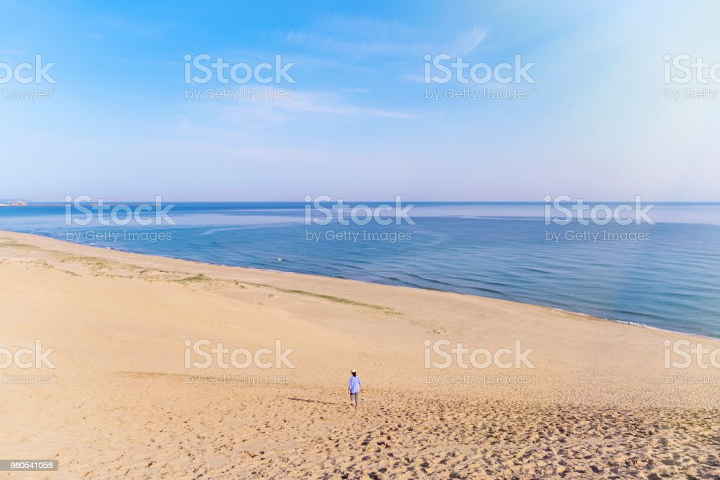 Women traveler walking in the sand dune looking at the sea stock photo