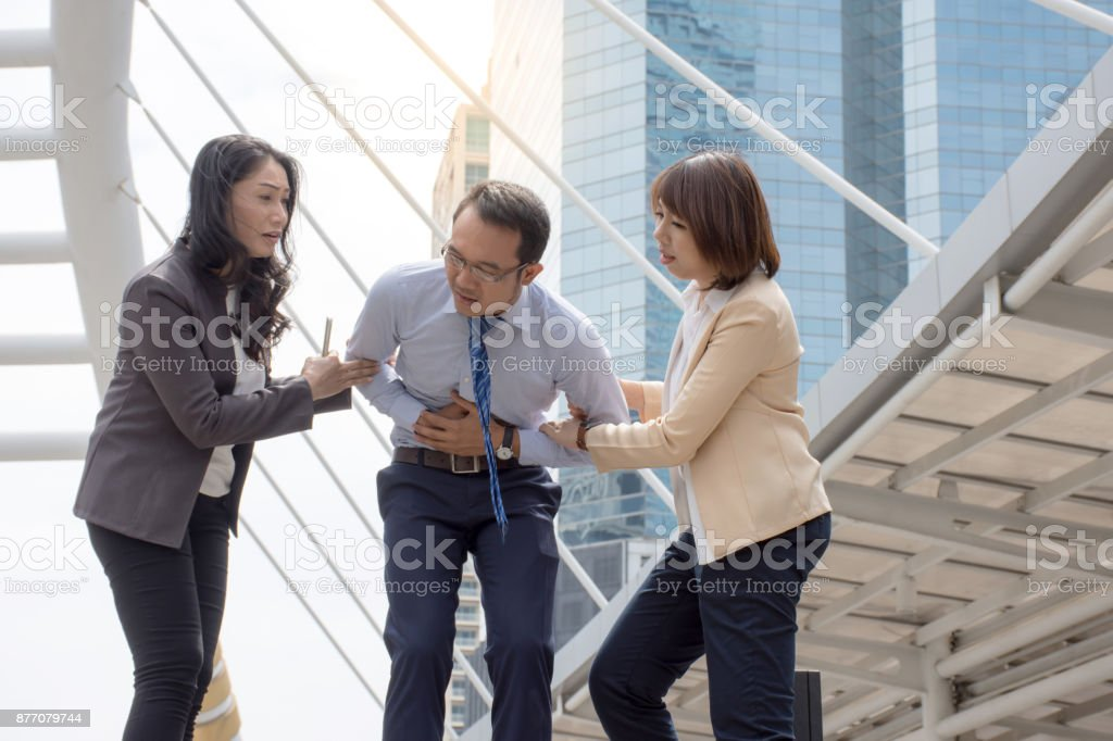 Women try to help her friend suffering from stomach ache standing stock photo