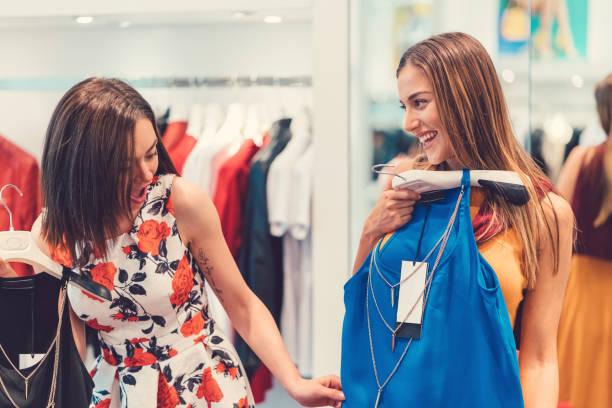 frauen, die versuchen auf neue kleider in der shopping mall - kleider günstig kaufen stock-fotos und bilder