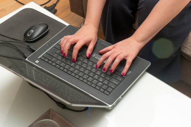 mujeres escribiendo en la computadora portátil en casa - gerente de cuentas fotografías e imágenes de stock