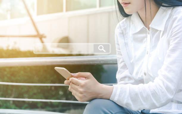 frauen nutzen smartphones, um zu finden, was sie interessiert. informationsdaten zum internet-netzwerkkonzept suchen - online lexikon stock-fotos und bilder