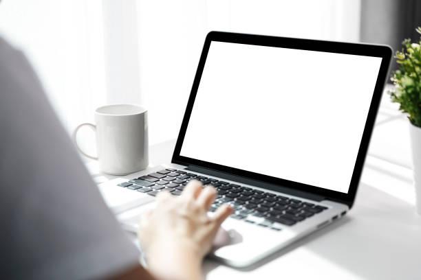 オフィスでのテーブルに空白の画面でノートパソコンを使用している女性は、ビジネスの女性がオフィスデスクでラップトップを使用して忙しい手のバックビュー。 - パソコン ストックフォトと画像