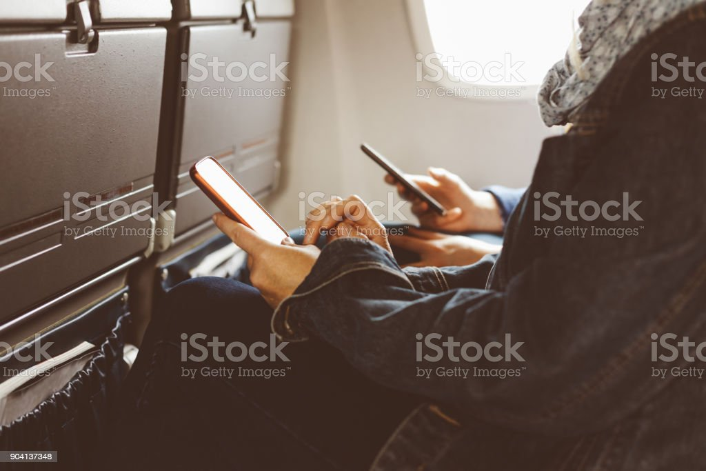 Women using smart phone while travelling by airplane stock photo