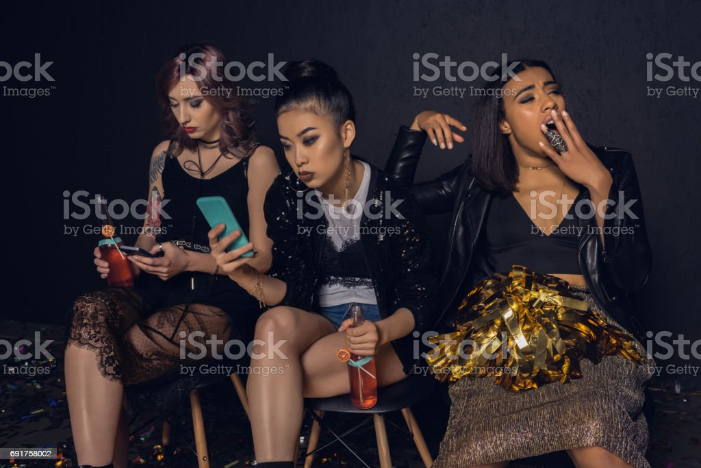 women using smartphones with bored friend near by at party stock photo