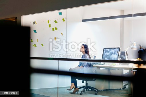 Women viewing ideas on notes in design studio at night