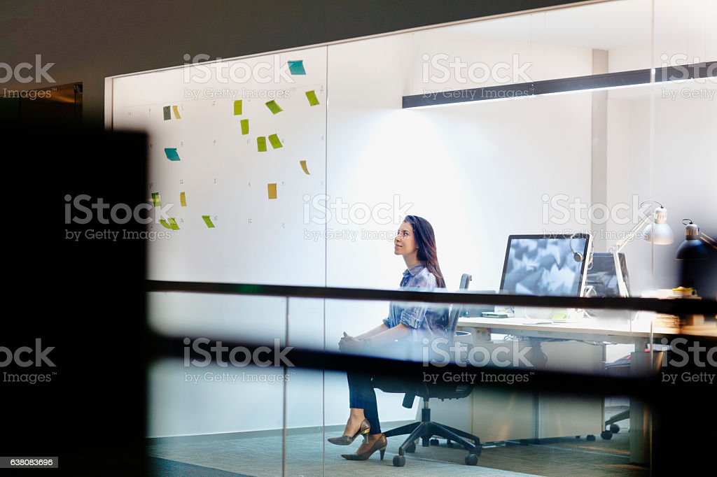 Women viewing ideas on notes in design studio at night - foto de stock