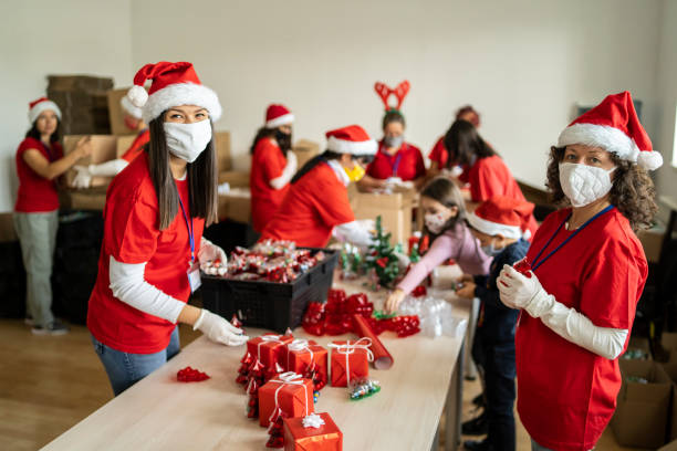 Women volunteering by preparation of Christmas presents for poor people in time of pandemic