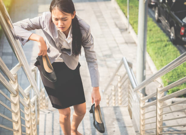 Women walk up the ladder with bare feet and Holding black high heels with fatigue. stock photo
