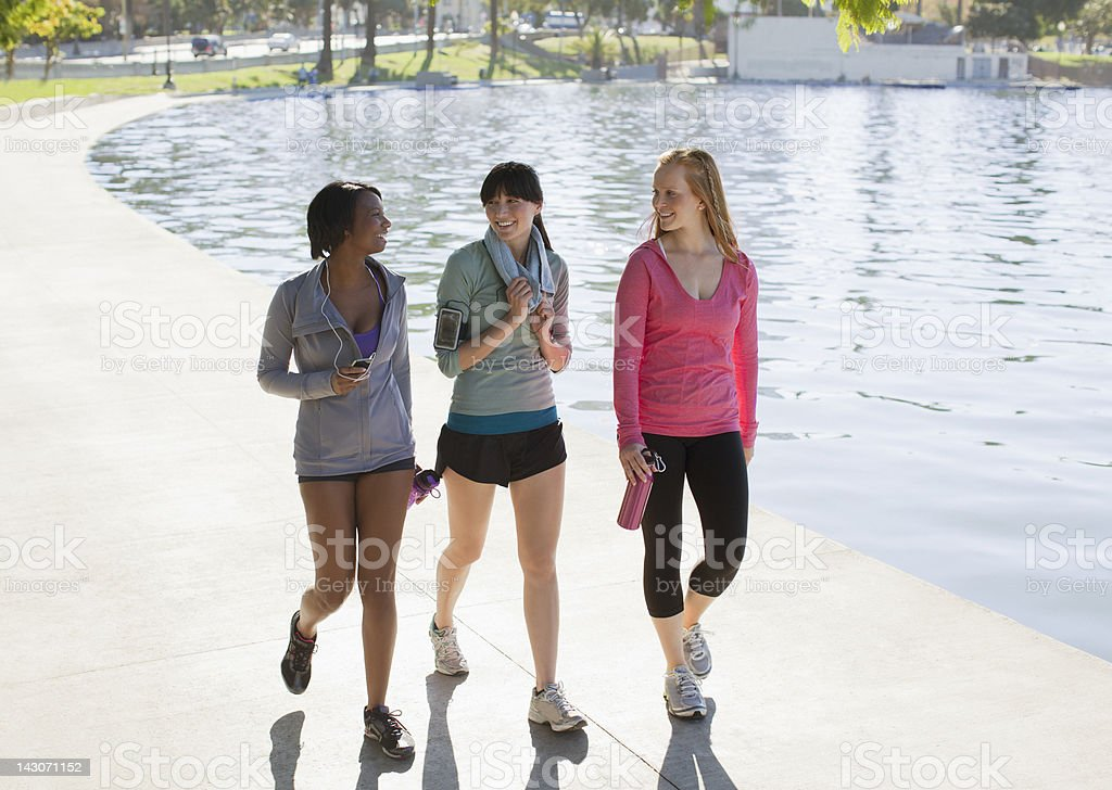Women walking along lake in park royalty-free stock photo