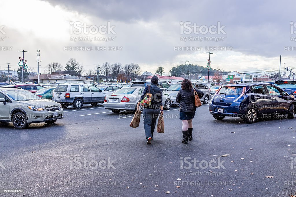 Women walking during snow fall with Trader Joes bags stock photo