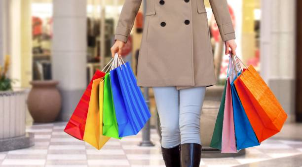 women walking in a mall with handfull of shopping bags - spending money stock photos and pictures