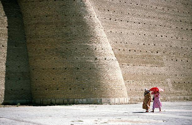women walking in front of a large wall, buchara, uzbekistan - oezbekistan stockfoto's en -beelden